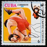 Two wrestlers don Olympic games in Moscow, Russia, circa 1980. MOSCOW, RUSSIA - APRIL 2, 2017: A post stamp printed in Cuba shows two wrestlers don Olympic games stock photo