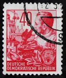 MOSCOW, RUSSIA - APRIL 2, 2017: A post stamp printed in DDR (Germany) shows scientist with a microscope, circa 1958 royalty free stock image