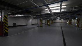 Underground car park with lots of empty space. Moscow, Russia - April 12, 2018: Rotating shot of underground parking garage with only one car parked and lots of stock video footage