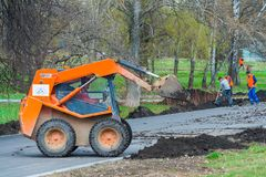 Works on the development of the park. Moscow, Russia, april 2018: Works on the development of the park area. Skid steer unloads black soil editorial royalty free stock photography