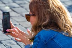 Back view on a woman, taking a photo on the phone royalty free stock images