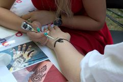MOSCOW, RUSSIA - AUGUST 12, 2018: girl gets picture at hand. MOSCOW, RUSSIA - AUGUST 12, 2018: girl inflicts intricate pattern on client`s hand with black henna stock photos