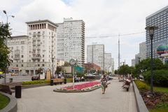 People resting near flower bed 20.08.2018. MOSCOW, RUSSIA - AUGUST 20, 2018: People resting near flower bed in Novy Arbat street. This street is located in the Stock Image