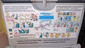 Moscow, Russia, August 5, 2018 Safety instruction aboard the Pobeda airplane. Emergency Landing and Evacuation on Water sign on. Safety instructions card in royalty free stock images