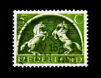 Rising Grey Horses, German symbols serie, circa 1943. MOSCOW, RUSSIA - AUGUST 18, 2018: A stamp printed in Netherlands shows Rising Grey Horses, German symbols royalty free stock photos