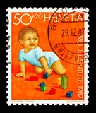 Young child playing with building blocks, Pro Juventute: Development of the child serie, circa 1987. MOSCOW, RUSSIA - AUGUST 18, 2018: A stamp printed in royalty free stock image