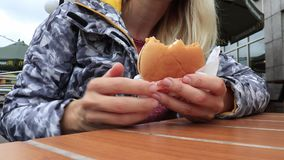 Moscow, Russia - August 02, 2019: Young woman eating a Cheeseburger hamburger menu in a McDonald`s restaurant stock video