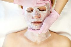 Moscow, Russia, 02.02.2019: Beautiful woman with facial mask at beauty salon. Applying facial mask at woman face at. Beautiful woman with facial mask at beauty stock image