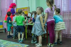 Children drawings around the table in the kindergarten. 2019.01.22, Moscow, Russia. Children drawings around the table in the kindergarten. Group of funny boys royalty free stock images