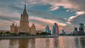 MOSCOW, RUSSIA - CIRCA AUGUST/2017: Moskva river view sunset timelapse. Tourist cruise boat embarkation in front of Radisson Royal, former Ukraina hotel, with stock video