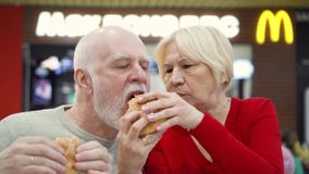 MOSCOW, RUSSIA- CIRCA JANUARY 2018: Hungry seniors eating hamburger at McDonald`s on food court