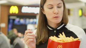 MOSCOW, RUSSIA - CIRCA November 2017: Hungry girl eating french fries at McDonald`s on food court stock footage