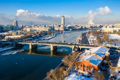 Winter view of Moskva river, Novospasskiy Bridge, and skyscrapers on a sunny morning. Ice floes, blocks of ice, snow on roofs. royalty free stock image