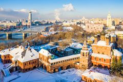 Winter view of Moskva river, Novospasskiy Bridge, and skyscrapers on a sunny morning. Krutitsy Metochion. Ice, snow on roofs. stock photography