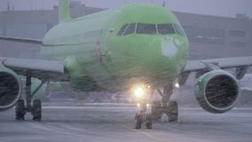 Plane of S7 Airlines driving on runway at Domodedovo Airport, view in snowfall. Moscow, Russia - December 18, 2017: Airbus A-321 of S7 Airlines turning to the stock footage