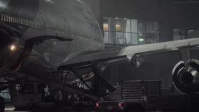 Boeing 747-400 of Thai Airlines is prepared for unloading baggage at night. MOSCOW, RUSSIA - DECEMBER 18, 2017: Arrived Thai Boeing 747-400 being prepared for stock video footage