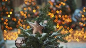 MOSCOW, RUSSIA - DECEMBER 6: Beige plastic christmas star on fir tree pan shot. Bokeh effect on the background stock footage