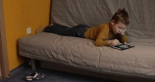 Kid entertaining himself with touch pad at home. MOSCOW, RUSSIA - DECEMBER 02, 2016: Boy with model release lying on the sofa at home and spending free time with stock footage