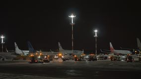 Snow plough trucks cleaning tarmac in Vnukovo Airport at night, Moscow. MOSCOW, RUSSIA - DECEMBER 25, 2017: Night view of Vnukovo Airport with planes of Utair stock video footage