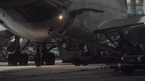 Unloading arrived Boeing 747-400 at night. MOSCOW, RUSSIA - DECEMBER 18, 2017: Panning shot of the airport with staff and vehicles unloading Boeing 747-400. View stock video