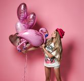 MOSCOW, RUSSIA, DECEMBER 2018 - Shapely girl in white t-shirt and cute hat holding colorful balloons for party royalty free stock images