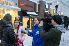 Moscow, Russia - February 11, 2018. Correspondent of TV and radio company Mir takes interview with passers-by on Old Arbat. Moscow, Russia - February 11, 2018 Royalty Free Stock Images