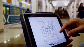 Man in underground examines the subway map using the tablet. Moscow, Russia - February 11, 2018: Man in underground examines the subway map using the tablet stock video