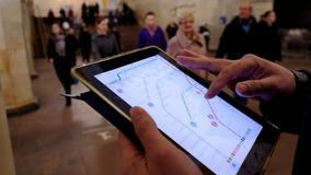 Man in underground examines the subway map using the tablet. Moscow, Russia - February 11, 2018: Man in underground examines the subway map using the tablet stock footage