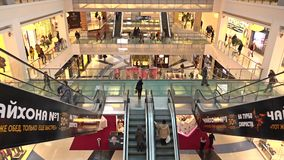 MOSCOW, RUSSIA - FEBRUARY, 28, 2017. Moving staircases and stores of modern shopping mall Metropolis. 4K clip stock video footage