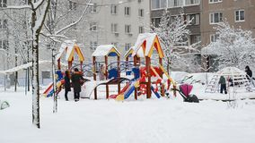 Moscow, Russia - February 4. 2018. Parents walk with children on playground in winter. Moscow, Russia - February 4, 2018. Parents walk with children on the stock video footage