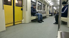 MOSCOW, RUSSIA - FEBRUARY, 28, 2017. Passengers reading and using mobile devices in departing subway train. 4K video. MOSCOW, RUSSIA - FEBRUARY, 28, 2017 stock video footage
