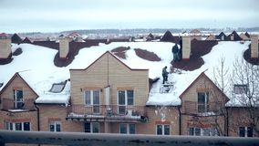 MOSCOW, RUSSIA - FEBRUARY, 20, 2017. Shoveling snow from the sloped roof after heavy snowfall. MOSCOW, RUSSIA - FEBRUARY, 20, 2017 Shoveling snow from the roof Royalty Free Stock Photo