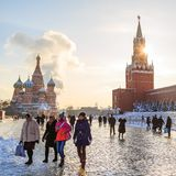 Tourists from different countries stroll through Red Square and take photos against the background of St. Basil`s Cathedral and th stock images
