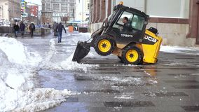 Snow cleaning tractor. MOSCOW, RUSSIA - FEBRUARY 09, 2018: Tractor cleaning up the street after the night snowfall in February 2018 in Moscow Russian Federation stock video footage