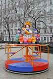 Traditional Dymkovo toy Mother with children as art object and Children`s carousel at Russian national festival `Shrove` in Moscow Royalty Free Stock Photo