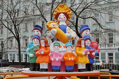 Traditional Dymkovo toy Mother with children as art object and Children`s carousel at Russian national festival `Shrove` in Moscow Royalty Free Stock Photos