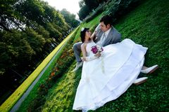 Groom and bride lying on grass and royalty free stock photo