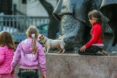 Group of girls and a dog playing around monument in the park. 2010.04.11, Moscow, Russia. Group of girls and a dog playing around monument in the park royalty free stock image