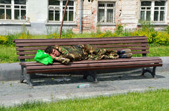 Moscow, Russia, June, 12, 2017, Homeless man sleeping on a bench on Khitrovskaya square in the summer in Moscow stock images