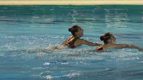 Performance of girls synchronized swimmers. Moscow, Russia - January, 2017: performance of two girls synchronized swimmers stock video