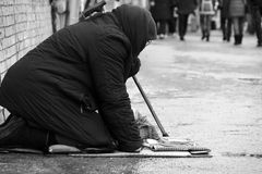 Moscow.Russia.-January 2018.Sad homeless woman sitting on the street people passing by. Black-and-white photo. Sad homeless woman sitting on the street people Royalty Free Stock Image