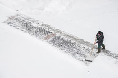 MOSCOW, RUSSIA - JANUARY 17, 2016: Worker removes snow from road. MOSCOW, RUSSIA - JANUARY 17, 2016: Worker in uniforms removes snow in the city Royalty Free Stock Image