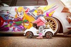 Moscow, Russia: July 06, 2019: Baby sits on a toy vehicle near tuned by low suspension and custom colored wheels. White volkswagen