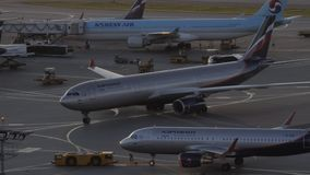 Airplanes pushback and boarding at Sheremetyevo Airport in Moscow, Russia. Moscow, Russia - July 24, 2018: Busy Sheremetyevo Airport. Pushback of Aeroflot A320 stock footage
