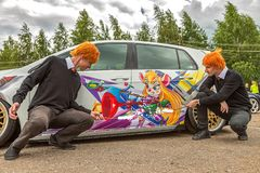 Moscow, Russia: July 06, 2019: Cosplay. Weasley brothers make magic painting on a tuned and lowrider volkswagen golf 7. Chip and