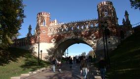 People walk near bridge of red brick in Tsaritsinsky park in summer. stock video