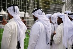 Football fans from Qatar. Moscow, Russia - July 14, 2018: Qatari men in traditional clothes watch the game on a football stadium. Qatar is the successor to royalty free stock photos