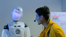 Funny humanoid robot with display face talking with guide man. MOSCOW, RUSSIA - July 30, 2018: Robostation - future exhibition. Funny humanoid robot with display royalty free stock photo