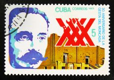 Man and building, 30th anniversary of the heroic assault on the Moncada barracks, circa 1983. MOSCOW, RUSSIA - JULY 15, 2017: A stamp printed in Cuba shows man stock photography