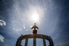Statue of an angel and the sun above it royalty free stock images
